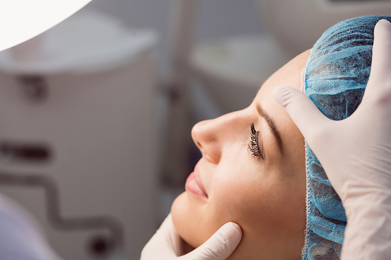 Hands of doctor examining womans face for cosmetic treatment at clinic